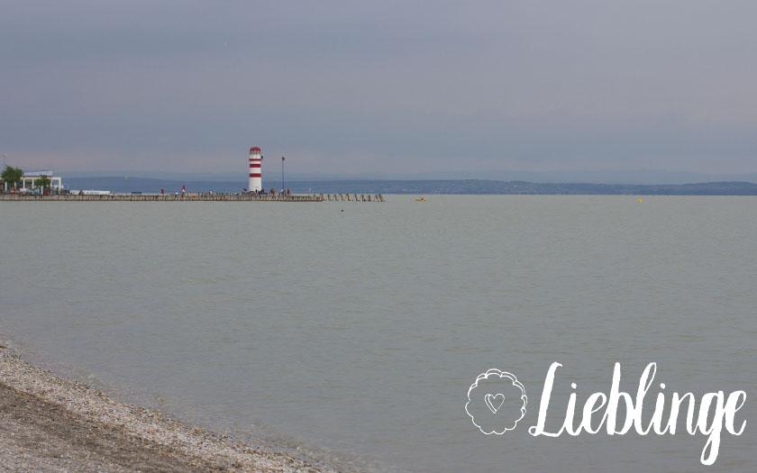 ausblick auf den grauen neusiedlersee, leuchtturm im hintergrund, lieblinge-schriftzug und lieblingsplätzchen-logo im vordergrund