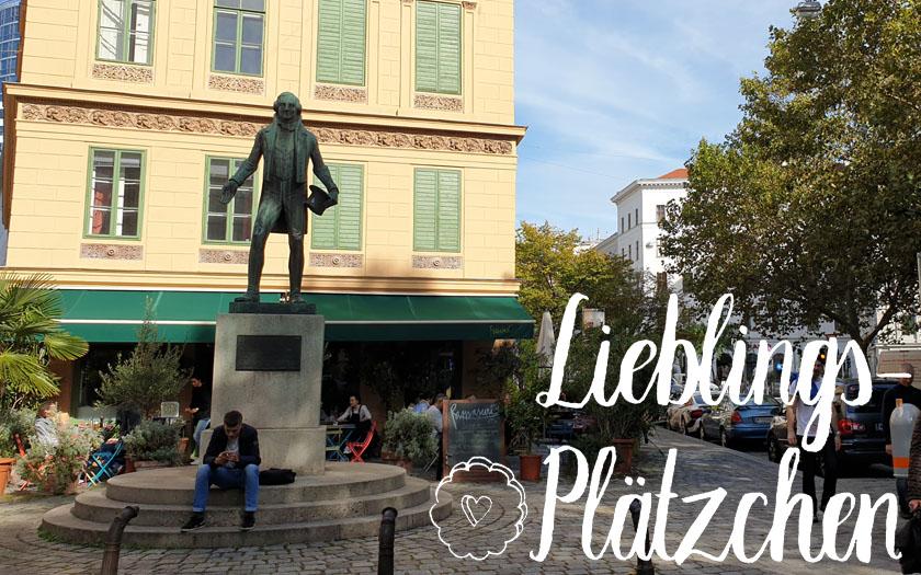 """nestroy-statue vor einem gelben haus, im vordergrund der """"lieblings-plätzchen""""-schriftzug"""