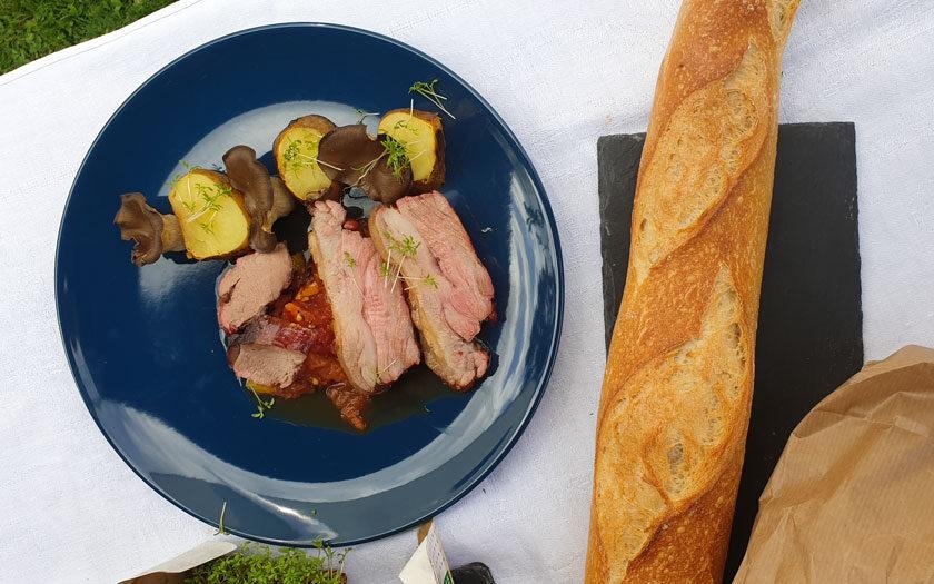 Ein Teller mit Fleisch, Letscho, Erdäpfeln und Pilzen, daneben Baguette